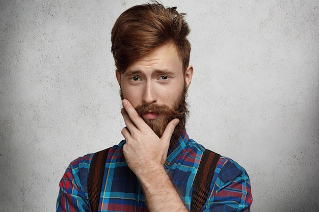 Retrato de hombre barbudo de moda vestido con camisa de franela y tirantes con mirada dudosa y burlona, tocando su espesa barba mientras pensaba en algo mientras posaba contra una pared en blanco