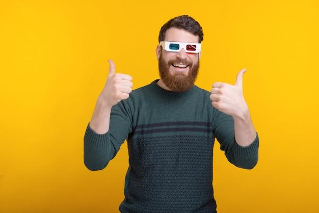 Retrato de hombre barbudo mostrando los pulgares hacia arriba y con gafas 3d