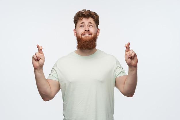 Retrato de hombre barbudo pelirrojo, viste camiseta en blanco, cruzó los dedos y reza por un buen resultado en blanco