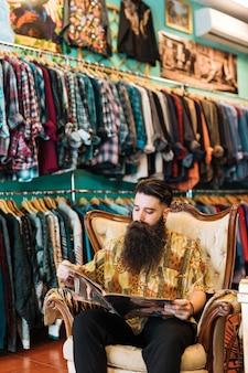 Retrato de un hombre barbudo que se sienta en la silla antigua del brazo que mira la revista en tienda de ropa