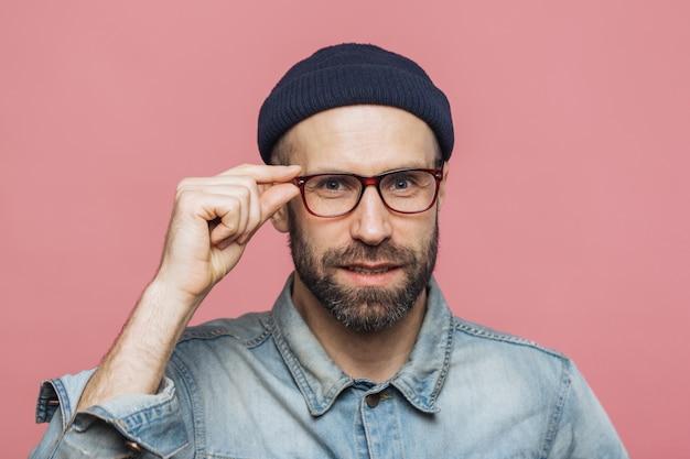 El retrato de un hombre barbudo satisfecho y de aspecto agradable con aspecto agradable mira con confianza a través de las gafas