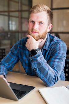 Retrato de hombre barbudo sentado frente a la computadora portátil en el lugar de trabajo