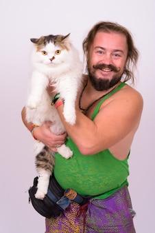 Retrato de hombre barbudo con sobrepeso con bigote y cabello largo sosteniendo gato persa contra la pared blanca
