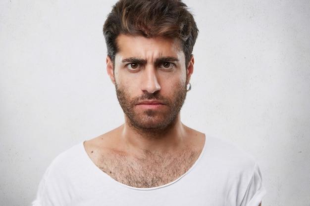 Retrato de hombre barbudo sombrío serio con peinado elegante de cerca. chico guapo con ojos oscuros frunciendo el ceño mostrando su insatisfacción