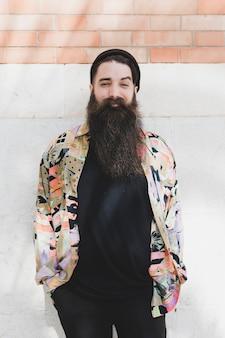 Retrato de un hombre barbudo sonriente contra la pared de ladrillo