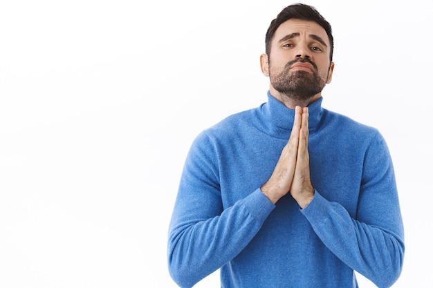 Retrato de hombre barbudo triste y pegajoso que se siente desesperado, pidiendo ayuda desesperadamente, tomados de la mano en oración, suplicando con necesidad, de pie suplicando pared blanca