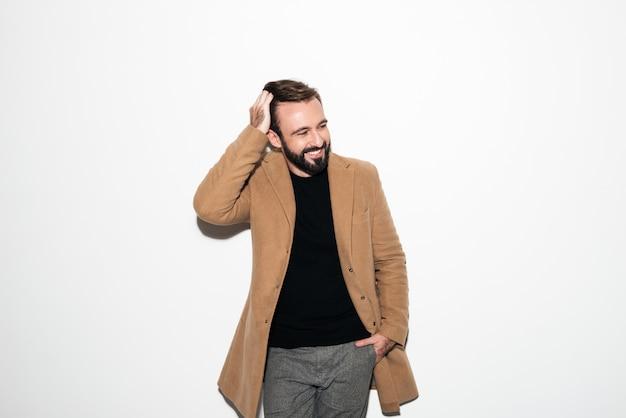 Retrato de un hombre barbudo vestido con un abrigo riendo