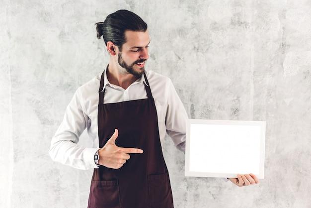 Retrato de hombre barista guapo barista hombre propietario de una pequeña empresa sonriendo y sosteniendo tablero vacío marco de madera con maqueta blanca en blanco en un café
