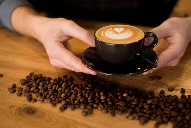 Retrato de hombre barista profesional en delantal con taza de café caliente en un café