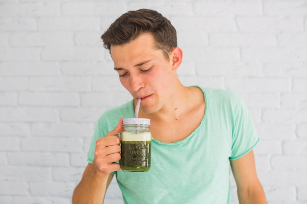 Retrato de un hombre bebiendo batidos verdes frescos en jarra