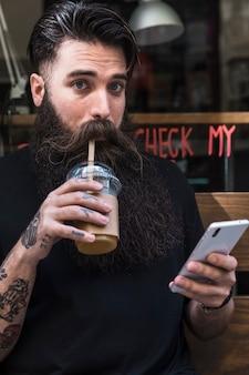 Retrato de un hombre bebiendo el chocolate con leche con el teléfono móvil en la mano