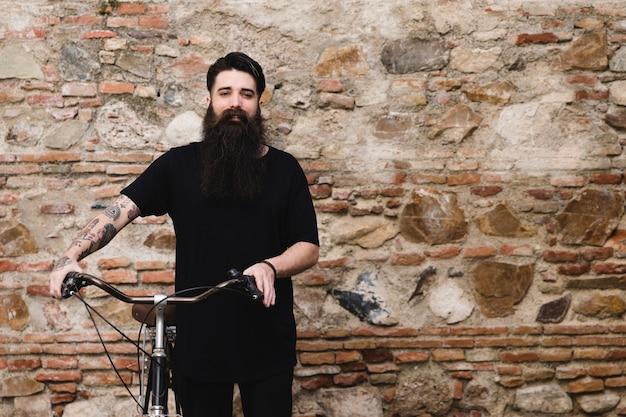 Retrato de un hombre con la bicicleta de pie delante de la pared abandonada