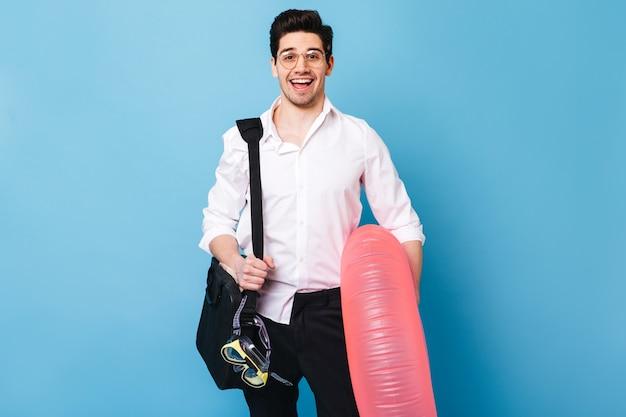 Retrato de hombre brunet con camisa blanca y pantalón negro. guy está sonriendo y sosteniendo un anillo de goma, una máscara de buceo y una bolsa para documentos.