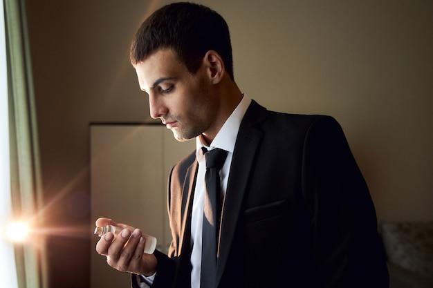 Retrato de un hombre brutal con colonia en sus manos, fragancia de perfume para hombres reales, perfumería cosmética. botella de perfume de colonia. botella de colonia de moda rich man