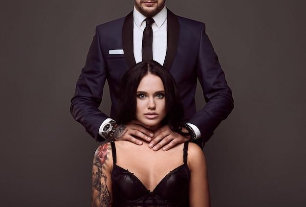 Retrato de un hombre brutal en traje elegante toca a una chica sexy con un tatuaje en lencería en la pared gris