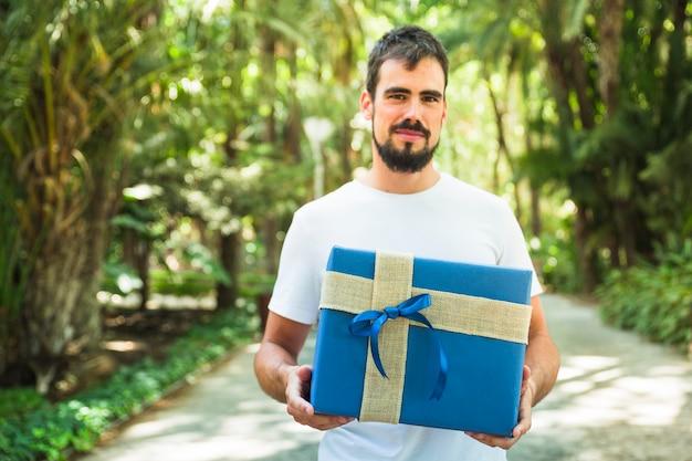 Retrato de un hombre con caja de regalo azul en el parque