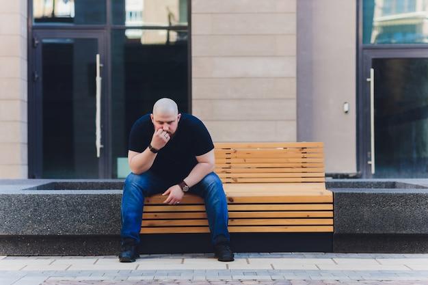 Retrato de un hombre calvo y guapo con barba en una camiseta negra en la calle, que mira hacia otro lado.