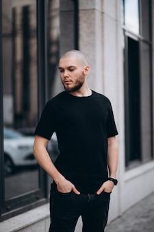 Retrato de un hombre calvo y guapo con barba en una camiseta negra en la calle, que mira hacia otro lado