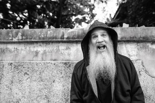 Retrato de hombre calvo maduro con larga barba gris contra el muro de hormigón de grunge al aire libre en blanco y negro