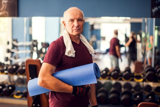Un retrato de hombre calvo senior manteniendo estera de yoga y mirando a cámara. concepto de personas, salud y estilo de vida
