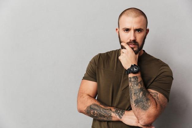 Retrato de hombre calvo varonil con tatuaje en los brazos mirando y sosteniendo la barbilla, aislado sobre la pared gris Foto Premium