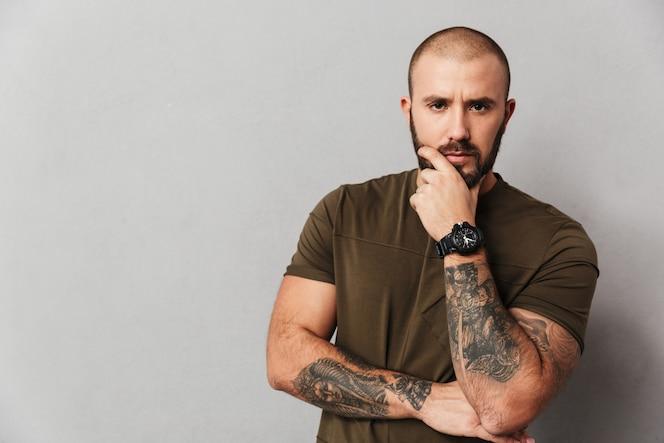 Retrato de hombre calvo varonil con tatuaje en los brazos mirando y sosteniendo la barbilla, aislado sobre la pared gris