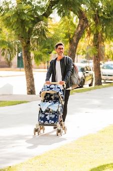 Retrato de un hombre caminando con carro de bebé en la calle de la ciudad