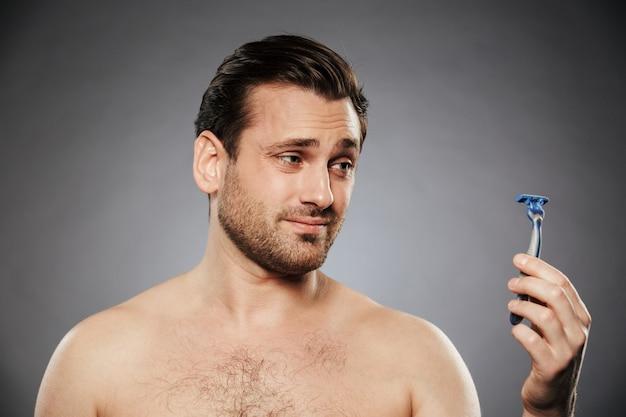 Retrato de un hombre sin camisa confundido mirando maquinilla de afeitar