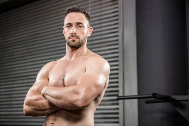 Retrato de hombre sin camisa de pie con los brazos cruzados en el gimnasio de crossfit