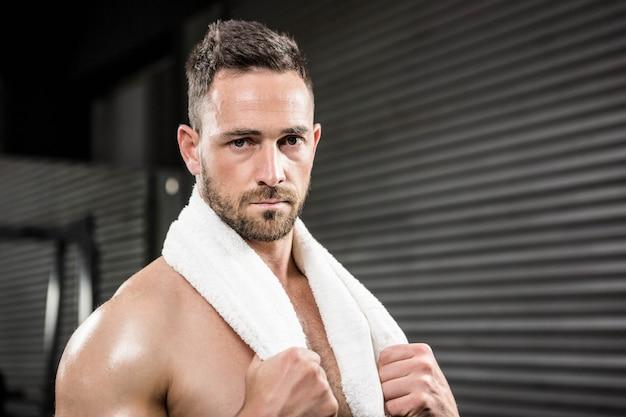 Retrato de hombre sin camisa con una toalla alrededor del cuello en el gimnasio de crossfit