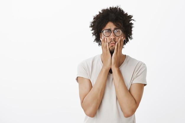Retrato de hombre cansado y molesto con gafas, ojos en blanco y cara con la palma molesta