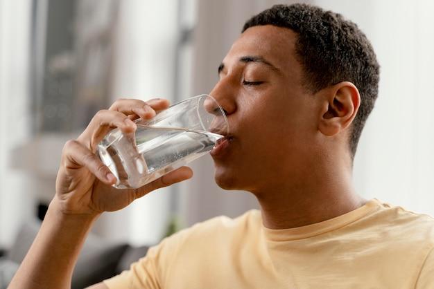 Retrato de hombre en casa bebiendo un vaso de agua