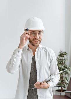 Retrato de hombre con casco en la oficina