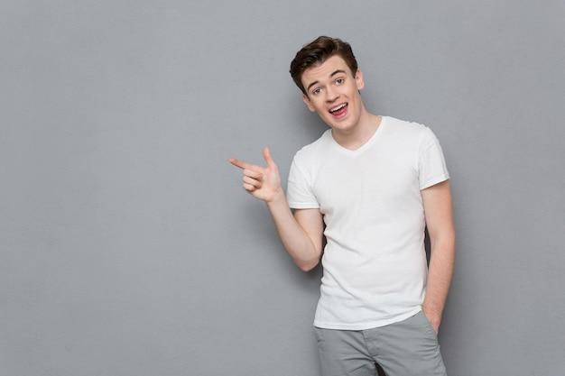 Retrato de hombre casual atractivo inspirado guapo en camiseta blanca y pantalón gris apuntando hacia fuera en copyspace