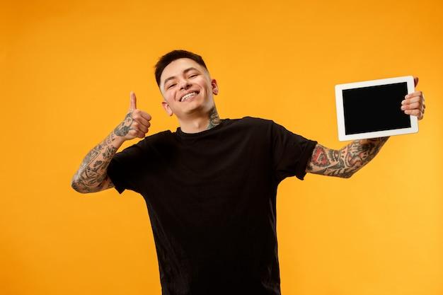 Retrato de un hombre casual confidente que muestra la pantalla en blanco de la computadora portátil