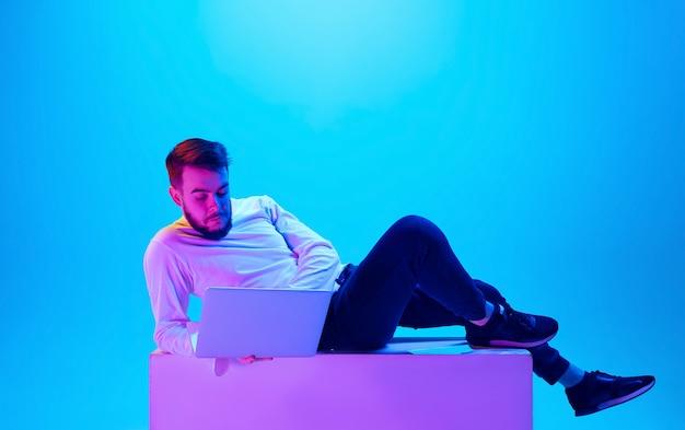 Retrato de hombre caucásico aislado sobre fondo azul de estudio en luz de neón. hermoso modelo masculino. concepto de emociones humanas, expresión facial, ventas, publicidad. copyspace para anuncio.