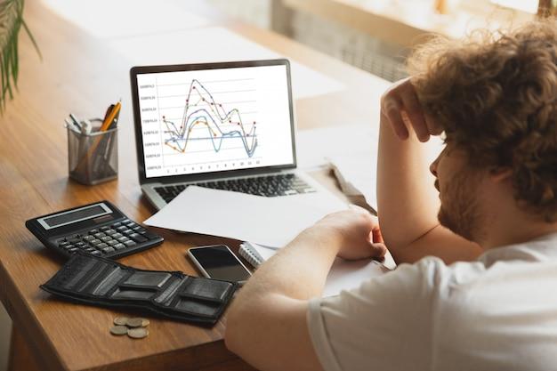 Retrato de hombre caucásico desesperado y desesperado viendo gráficos financieros y económicos durante la cuarentena de coronavirus, problemas