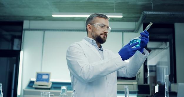 Retrato del hombre caucásico con gafas y túnica blanca haciendo un análisis del líquido azul en el tubo de ensayo durante la investigación médica o farmacéutica en el laboratorio.