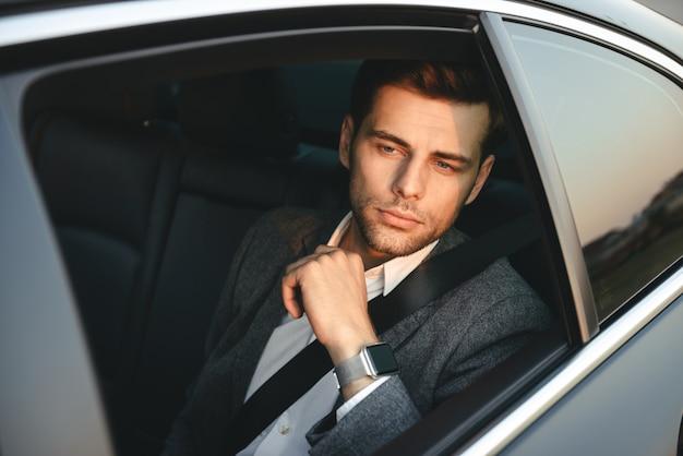 Retrato de hombre caucásico guapo vistiendo traje profesional, sentado mientras viajaba en coche con cinturón de seguridad