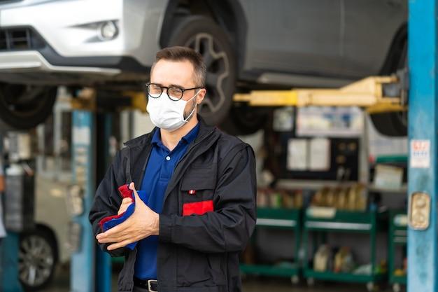 Retrato de hombre caucásico limpiando las manos con un paño y vistiendo mascarilla médica protección coronavirus .. mecánico de experiencia que trabaja en el garaje de reparación de automóviles.