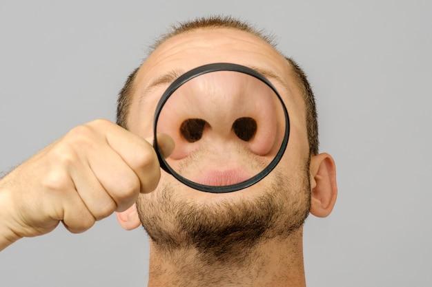 Retrato de hombre caucásico con lupa burla cara