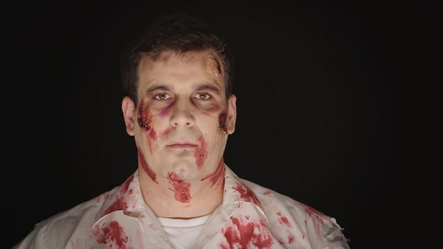 Retrato de hombre caucásico con maquillaje para halloween disfrazado de zombie.