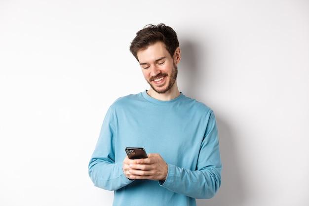 Retrato de hombre caucásico moderno con barba, vestido con ropa casual, leyendo la pantalla del teléfono inteligente y sonriendo, redes a través del teléfono móvil, de pie sobre fondo blanco.