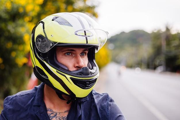 Retrato de hombre ciclista en casco amarillo en moto al lado de una carretera muy transitada en tailandia