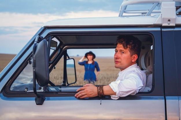 Retrato de hombre conduciendo un coche y una mujer caminando por el campo de trigo contra el fondo del cielo