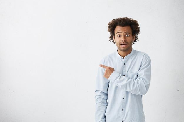 Retrato de hombre confundido gesticulando con mirada infeliz