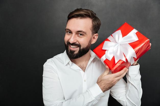 Retrato del hombre curioso que sacude la caja roja envuelta para regalo, y trata de reconocer lo que hay dentro sobre la pared gris oscuro