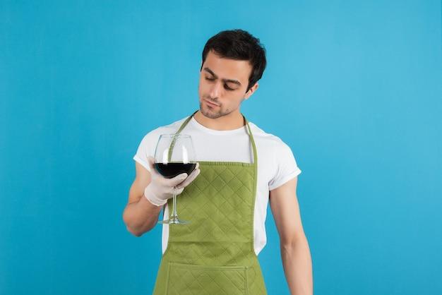 Retrato de hombre en delantal verde mirando una copa de vino tinto sobre pared azul