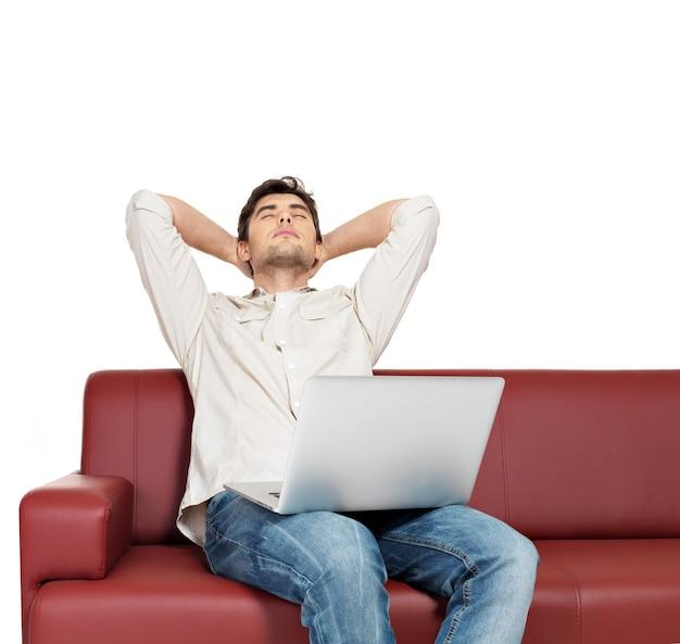 Retrato de hombre descansando con portátil se sienta en el diván, aislado en blanco.