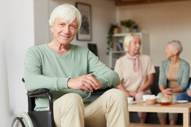 Retrato de hombre discapacitado senior sonriendo a la cámara con dos mujeres bebiendo té